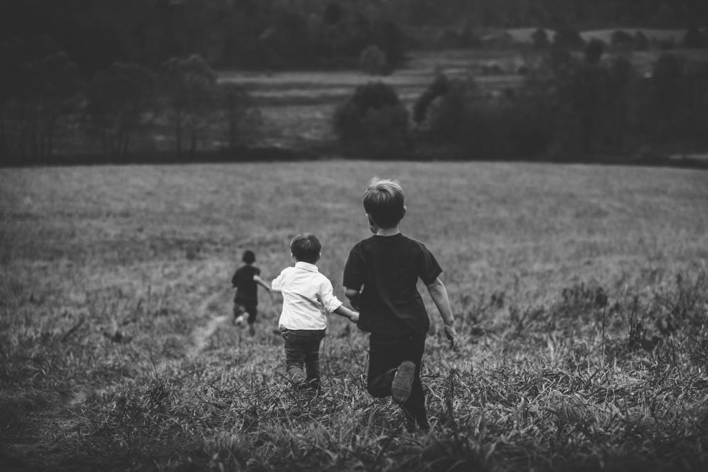 Black and white image of three boys running onto a field