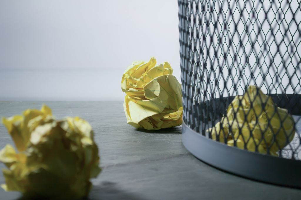 Image of yellow crumpled papers in and outside a gray wire wastebasket