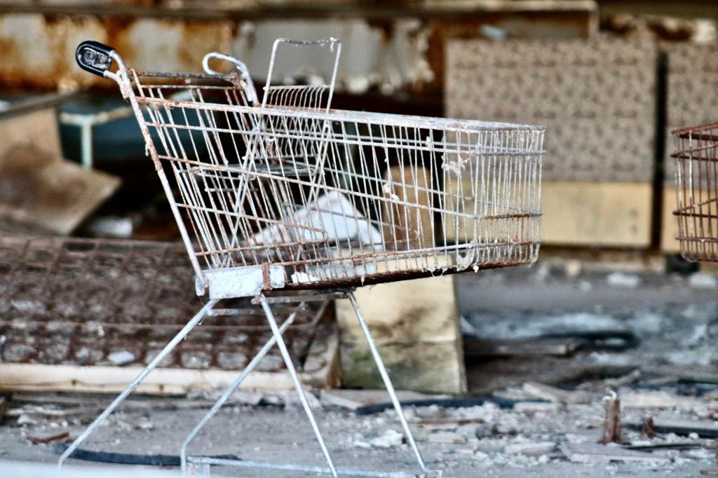 Image of gray metal shopping cart by concrete wall at daytime
