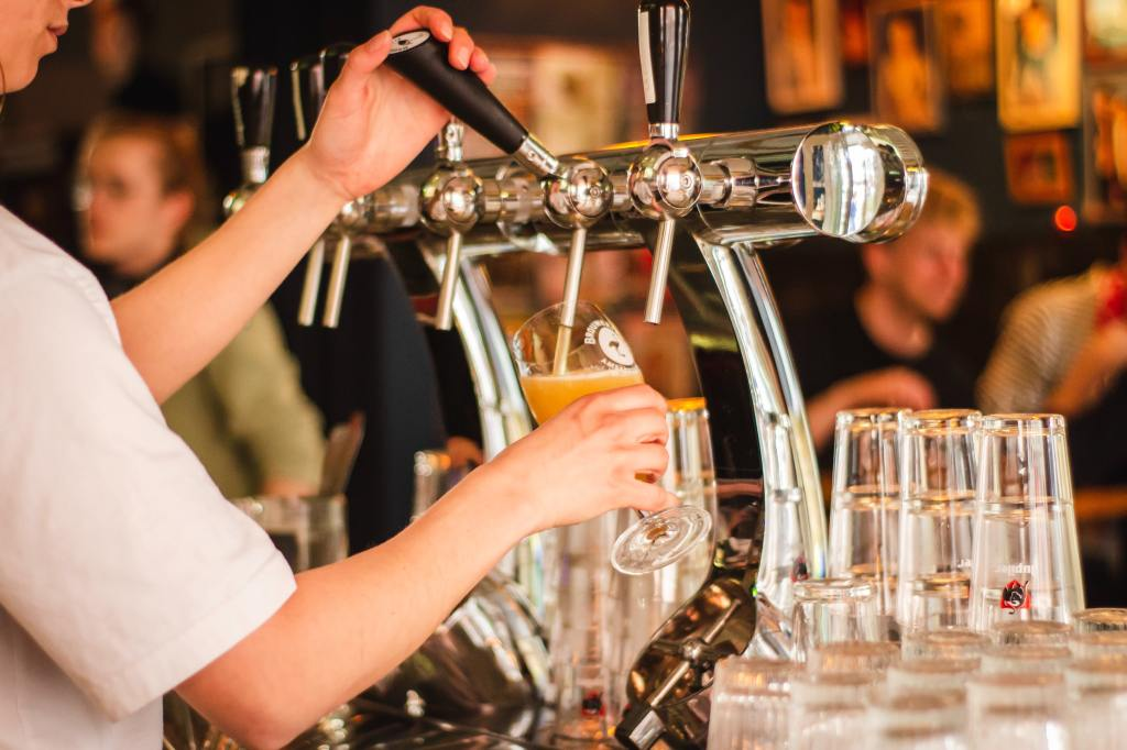 Image of person holding handle of beer tap