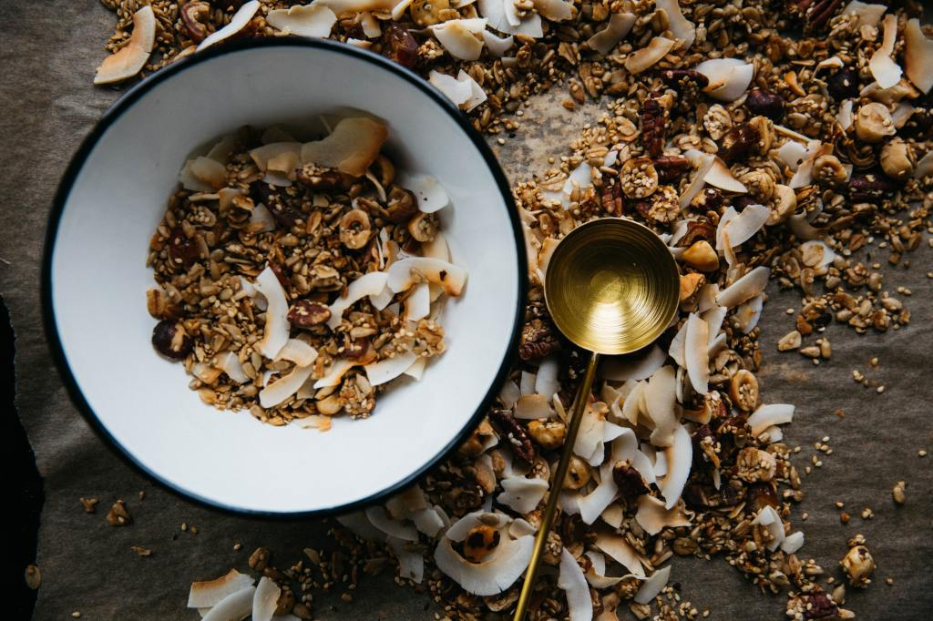 Image of a bowl with cereal with more cereal and metal spoon scattered around