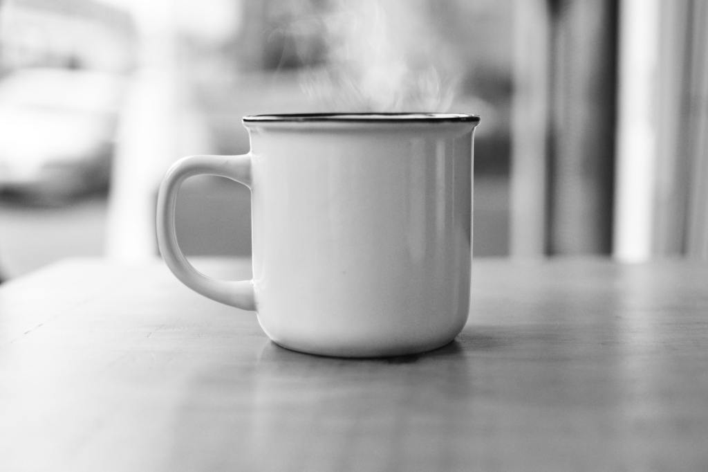 Black and white image of mug with steaming liquid inside