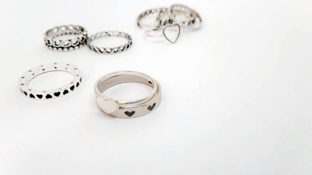 Image of white background with various silver rings in the foreground.