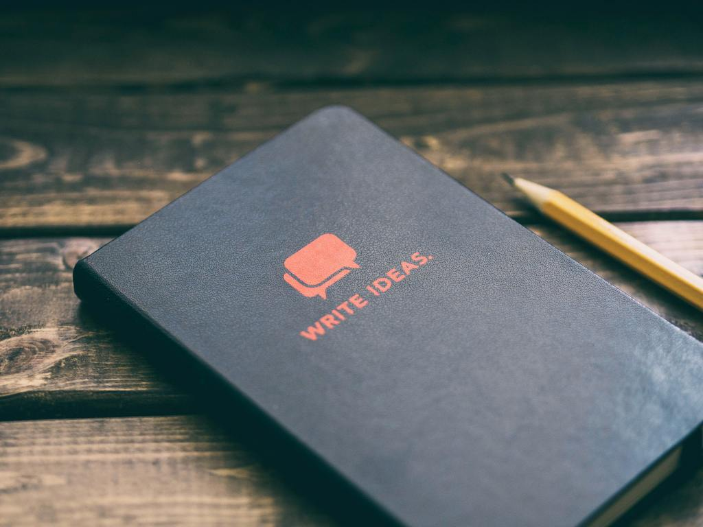 Image of a journal with 'Write Ideas' on the cover, and a pencil next to it, on a wooden surface.