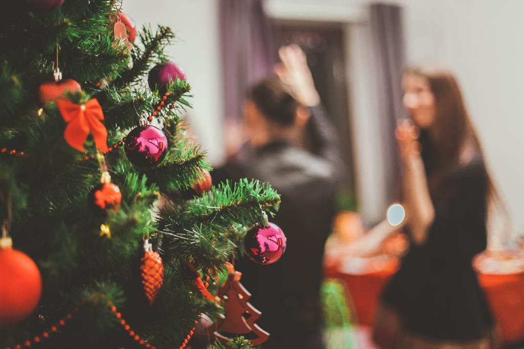 Image of an adorned Christmas treeing the foreground, with two people blurred out in the background.