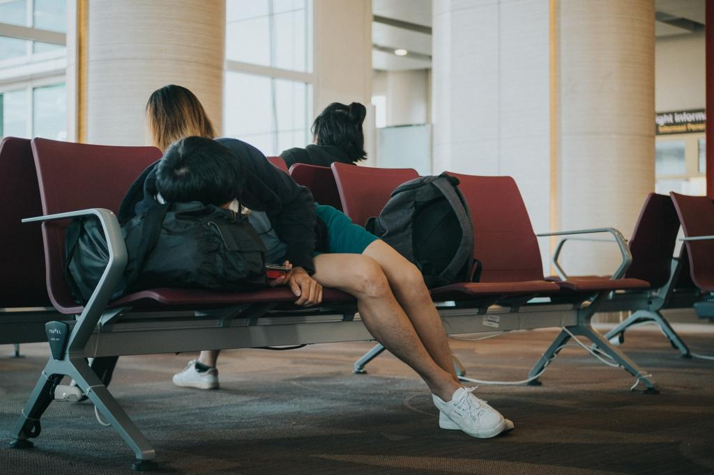 Image of person sitting in an airport waiting area, slumped on top of a suitcase.